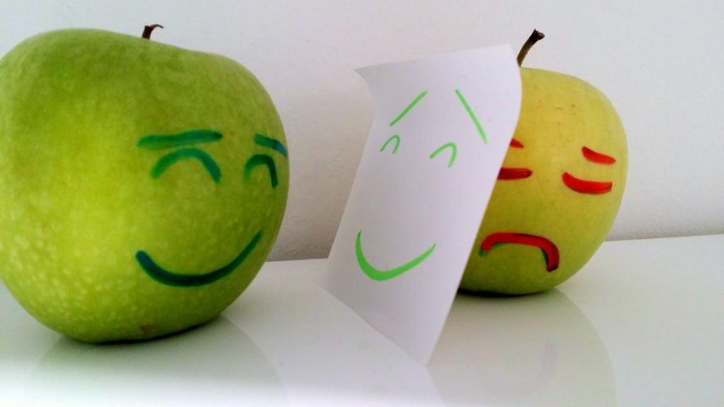 Apfel mit lachendem und weinendem Gesicht